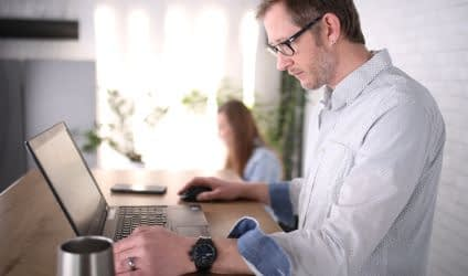 A man stood up against a high desk space working on his laptop