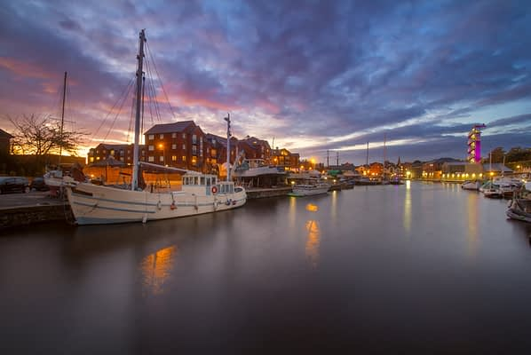 A white masted vessel is moored in a harbor in the city of Exeter. Other vessels are also visible. Colorful sunset. Exeter. Devon. England